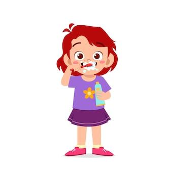 Śliczna mała dziewczynka myje zęby i trzyma pastę do zębów