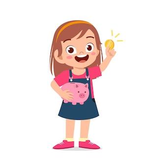 Śliczna mała dziewczynka nosi skarbonkę i złotą monetę
