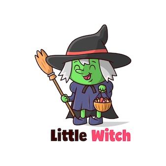 Śliczna mała dziewczynka ubrana w kostium czarownicy i przynosząca cukierki
