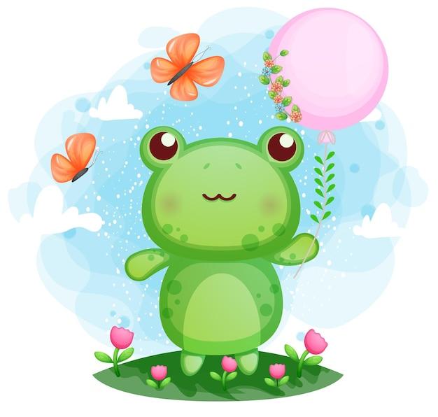 Śliczna mała żaba trzyma balon