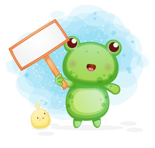 Śliczna mała żaba trzyma pustą tablicę tekstową