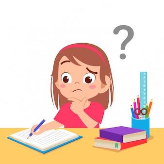 Śliczna małe dziecko dziewczyna zmieszana odrabia pracę domową