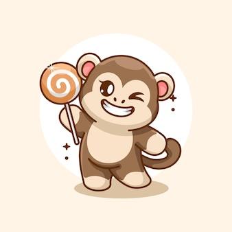 Śliczna małpa trzymająca kreskówkę z lizakiem