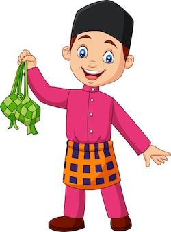 Śliczna muzułmańska chłopiec trzyma ketupat