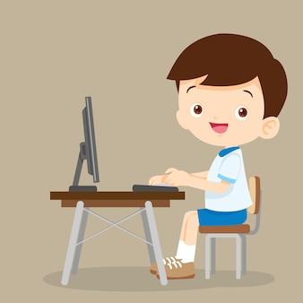 Śliczna studencka chłopiec pracuje z komputerem