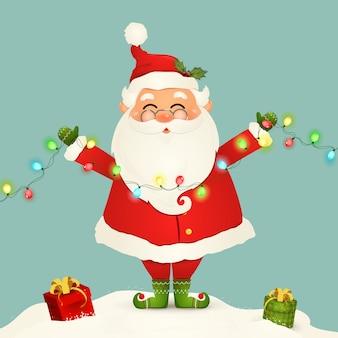 Śliczna święty mikołaj pozycja w śnieżnej mienia bożonarodzeniowe światła girlandzie odizolowywającej. śnięty mikołaj na zimowe i noworoczne świąteczne święta bożego narodzenia. postać z kreskówki szczęśliwy mikołaj.