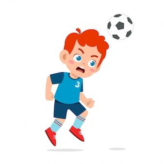 Śliczne dziecko chłopiec grać w piłkę nożną jako napastnik
