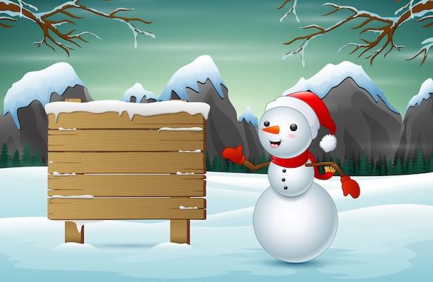 Śliczny bałwan i śnieżny drewniany znak