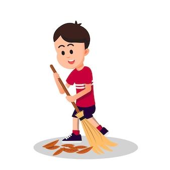 Śliczny chłopiec czyści ziemię z suchych liści