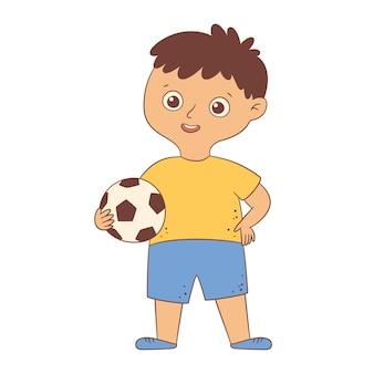 Śliczny chłopiec piłkarz stojący i trzymający piłkę w dłoni