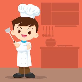 Śliczny chłopiec szef kuchni patrzeje mądrze