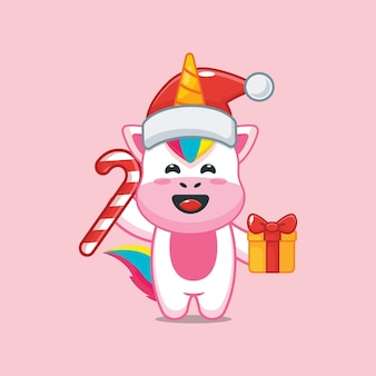 Śliczny jednorożec w boże narodzenie trzymający prezent świąteczny i cukierki śliczna świąteczna ilustracja kreskówka