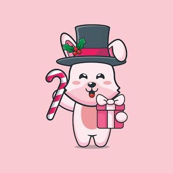 Śliczny króliczek w boże narodzenie trzymający prezent świąteczny i cukierki śliczna świąteczna ilustracja kreskówka