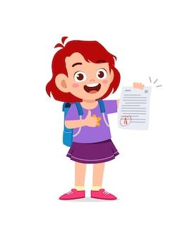 Śliczny mały chłopiec czuje się szczęśliwy, ponieważ dostaje dobrą ocenę z egzaminu