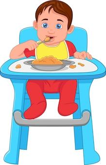 Śliczny mały chłopiec je na krześle