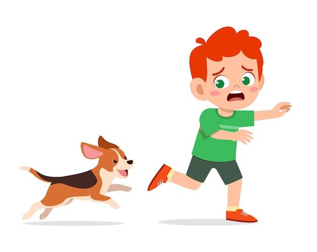 Śliczny mały chłopiec przestraszony przez złego psa