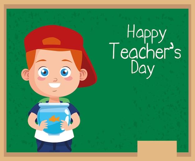 Śliczny mały chłopiec uczeń z napisem w tablicy szkolnej z akwarium i szczęśliwego dnia nauczyciela