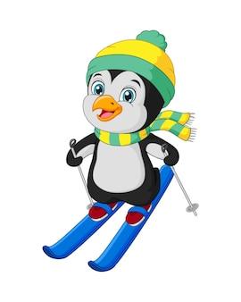 Śliczny mały pingwin na nartach w zimowych ubraniach