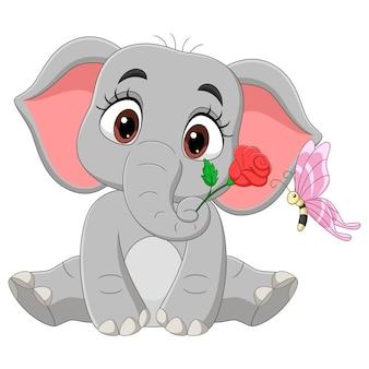 Śliczny mały słoń siedzi z kwiatami i motylem