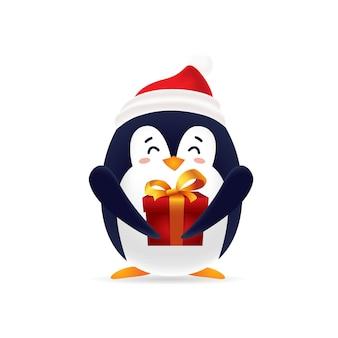 Śliczny pinguin z czerwoną nakrętką niesie prezenta pudełko na boże narodzenia z odosobnionym