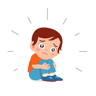 Śliczny smutny dzieciak chłopiec siedzi samotnie przestraszony