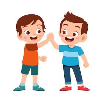 Śliczny szczęśliwy dzieciak robi ręki trząść z przyjacielem