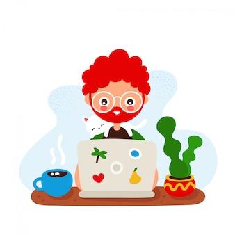 Śliczny szczęśliwy uśmiechnięty młody człowiek przy biurkiem z kotem i laptopem