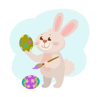 Śliczny wielkanocny królik maluje jajko