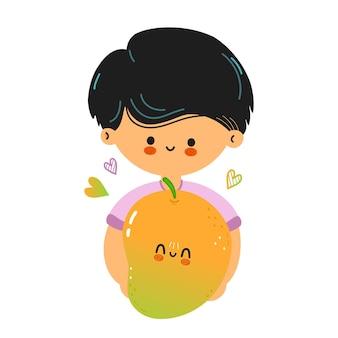 Śliczny zabawny chłopak trzyma mango w ręku