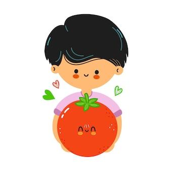 Śliczny zabawny chłopak trzyma pomidora w ręku