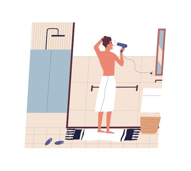 Śliczny zabawny młody człowiek stojący przed lustrem i suszący włosy suszarką do włosów
