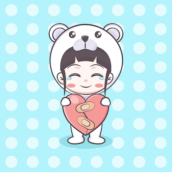Słodka dziewczyna kostiumowa niedźwiedzia polarnego trzymająca ilustrację kreskówki uzdrowionego paleniska