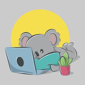 Słodka koala leży i obsługuje laptopa