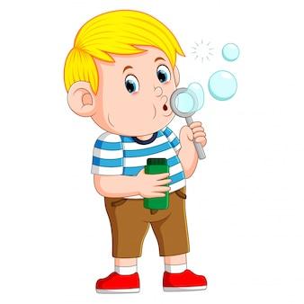Słodki chłopiec bawi się i dmucha w bańkę