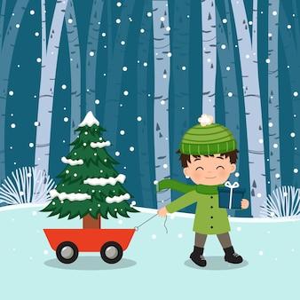 Słodki chłopiec ciągnący wózek z choinką, trzymający pudełko z prezentami