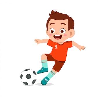 Słodki chłopiec gra w piłkę nożną jako napastnik