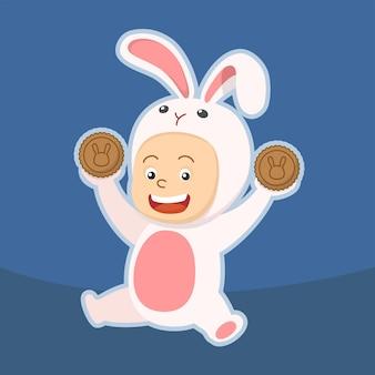 Słodki dzieciak w stroju królika trzymający dwa księżycowe ciasteczka w połowie jesieni
