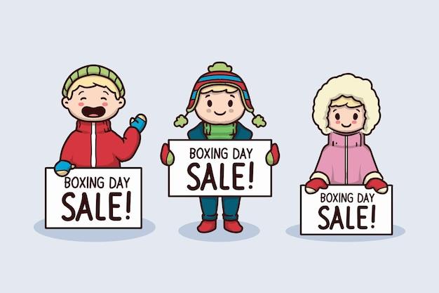 Słodki dzieciak z zimową odzieżą trzyma baner wyprzedaży na dzień świąteczny