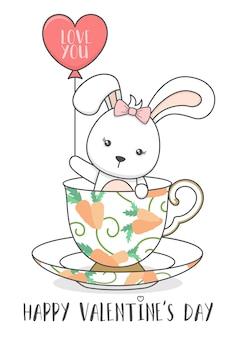 Słodki króliczek w filiżance trzymając balon
