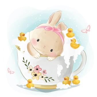 Słodki króliczek w wannie z filiżanką herbaty