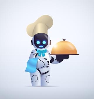 Słodki robot kucharz w kapeluszu trzymający klosz nowoczesna robotyczna postać gotująca w kuchni technologia sztucznej inteligencji