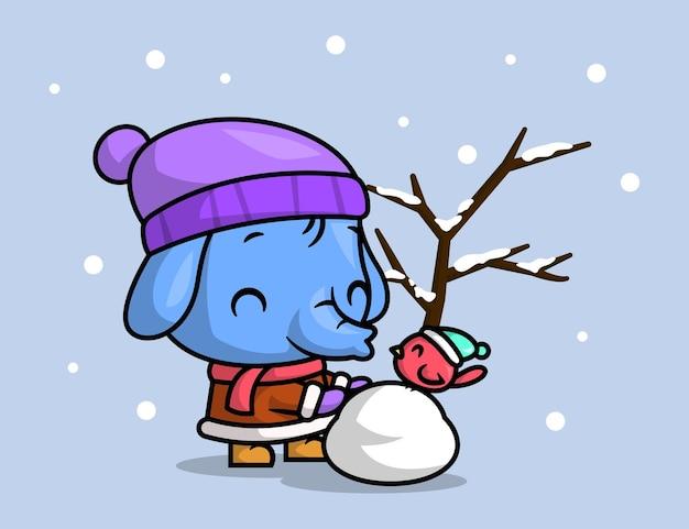 Słodki słoń z małym ptakem bawi się śnieżką na zewnątrz