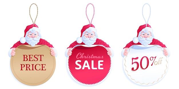 Słodki święty mikołaj przytula różne okrągłe metki z ceną. zestaw zawieszek cenowych z pętlami ze sznurka. kartonowe naklejki w kolorze brązowym, czerwonym i białym z napisem najlepsza cena, wyprzedaż świąteczna, 50% zniżki
