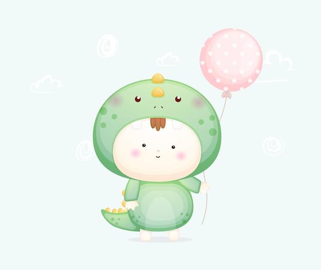 Słodkie dziecko w kostiumie dinozaura trzyma balon premium wektorów