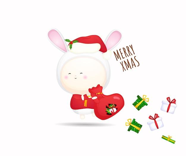 Słodkie dziecko w kostiumie niosącym worek prezentów na święta bożego narodzenia premium wektor