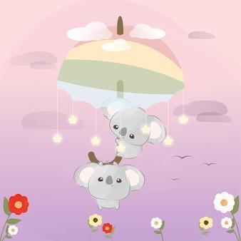Słodkie małe koale latające z tęczowym parasolem
