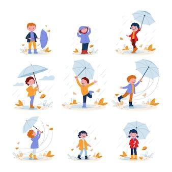 Słodkie uśmiechnięte dzieciaki z parasolkami w gumowych butach