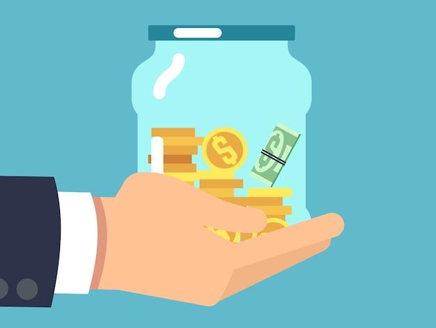 Słoik z pieniędzmi w ręku