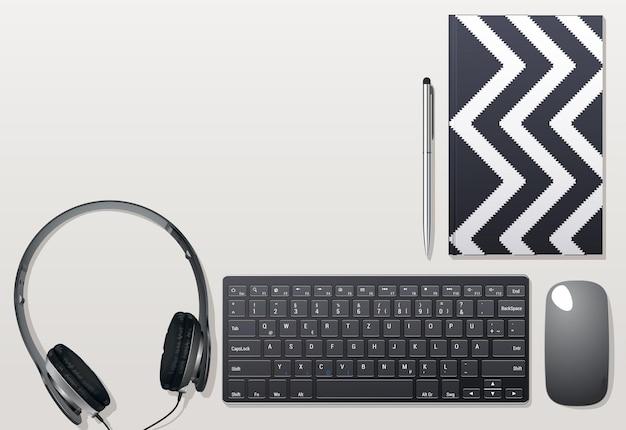 Słuchawki oraz klawiatura i mysz na pulpicie. mysz i notatnik z długopisem. materiały biurowe.