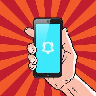 Smartfon w ręku z ikoną alarmu na ekranie